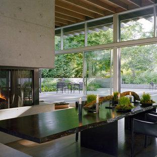 Cette photo montre une salle à manger moderne avec un manteau de cheminée en béton.