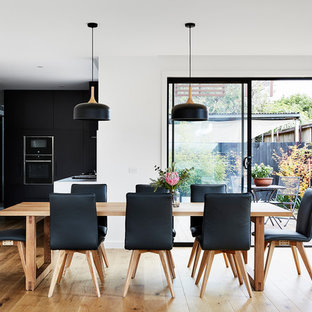 This is an example of a mid-sized contemporary kitchen/dining combo in Melbourne with white walls, medium hardwood floors and brown floor.