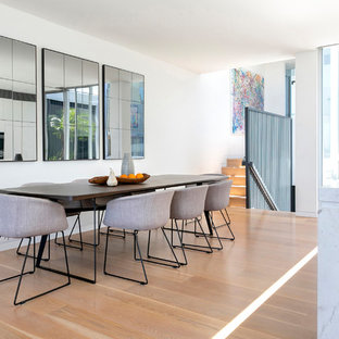 Large contemporary open plan dining in Sydney with white walls, medium hardwood floors and beige floor.