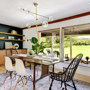 Example of a cottage light wood floor and beige floor enclosed dining room design in Austin with white walls