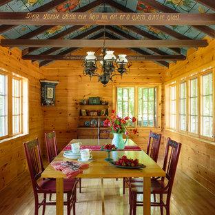 Esempio di una grande sala da pranzo country chiusa con parquet chiaro, pareti marroni, nessun camino e pavimento marrone