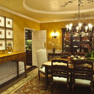 Immagine di una sala da pranzo tradizionale chiusa con pareti gialle e parquet scuro
