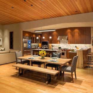 Esempio di una grande sala da pranzo aperta verso la cucina design con pareti beige, pavimento in legno massello medio, camino classico, cornice del camino piastrellata e pavimento marrone
