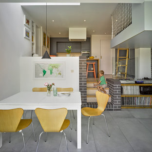 Inspiration for a medium sized contemporary open plan dining room in London with white walls and grey floors.