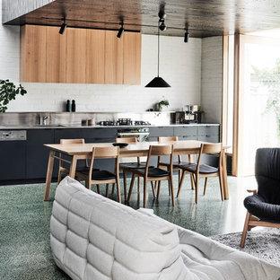 Foto di una sala da pranzo aperta verso il soggiorno moderna di medie dimensioni con pareti bianche, pavimento in cemento, nessun camino e pavimento verde