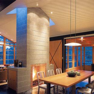 Imagen de comedor rural con marco de chimenea de hormigón