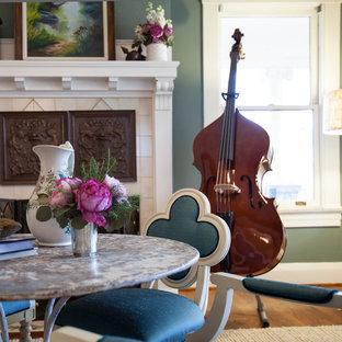 Esempio di una sala da pranzo aperta verso il soggiorno tradizionale di medie dimensioni con pareti verdi, pavimento in legno massello medio, camino classico e cornice del camino in cemento