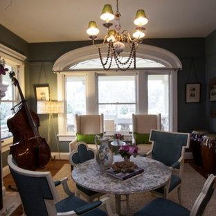 Imagen de comedor clásico, de tamaño medio, abierto, con paredes verdes, suelo de madera en tonos medios, chimenea tradicional y marco de chimenea de hormigón