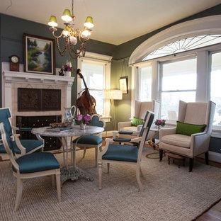 Diseño de comedor clásico, de tamaño medio, abierto, con paredes verdes, suelo de madera en tonos medios, chimenea tradicional y marco de chimenea de hormigón