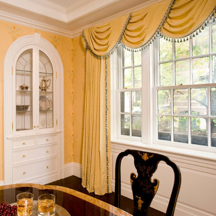 Photo of a medium sized classic dining room in Boston with yellow walls and dark hardwood flooring.