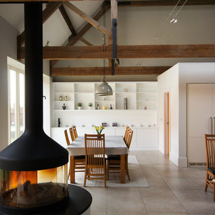 Design ideas for a large farmhouse open plan dining room in Oxfordshire with beige floors and a wood burning stove.
