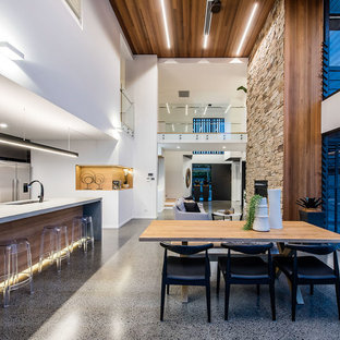 This is an example of a contemporary kitchen/dining combo in Brisbane with white walls and grey floor.