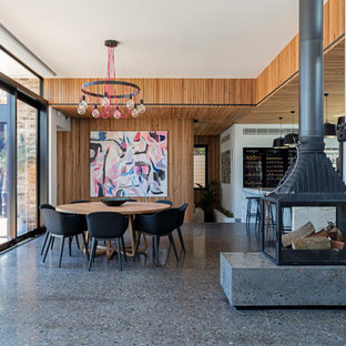 This is an example of a contemporary dining room in Sydney with concrete floors, white walls, a wood stove and a metal fireplace surround.