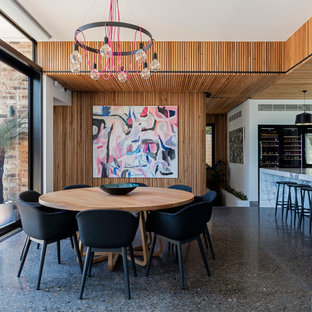 Photo of a mid-sized contemporary kitchen/dining combo in Wollongong with multi-coloured walls and concrete floors.