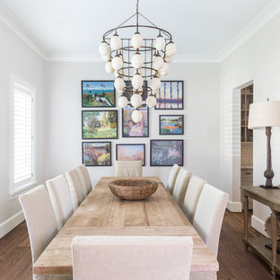 Inspiration for a timeless medium tone wood floor enclosed dining room remodel in Houston with white walls