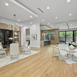 Große Moderne Wohnküche ohne Kamin mit weißer Wandfarbe, hellem Holzboden und gelbem Boden in Dallas