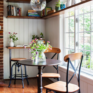 Kitchen/dining room combo - country medium tone wood floor and brown floor kitchen/dining room combo idea in Richmond with white walls, a standard fireplace and a brick fireplace