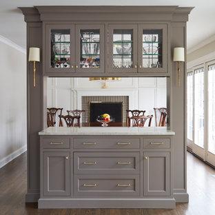 На фото: маленькая отдельная столовая в стиле неоклассика (современная классика) с серыми стенами, паркетным полом среднего тона, стандартным камином, фасадом камина из кирпича и коричневым полом с