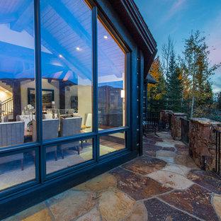 Выдающиеся фото от архитекторов и дизайнеров интерьера: большая гостиная-столовая в стиле рустика с бежевыми стенами, светлым паркетным полом, камином, фасадом камина из камня и коричневым полом