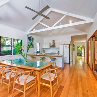 Photo of a tropical open plan dining in Gold Coast - Tweed with white walls and medium hardwood floors.