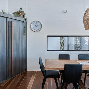 Идея дизайна: маленькая отдельная столовая в морском стиле с белыми стенами, паркетным полом среднего тона и коричневым полом