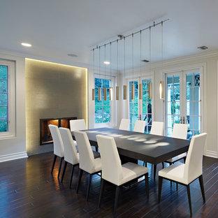 Foto di una grande sala da pranzo aperta verso il soggiorno contemporanea con pareti bianche, parquet scuro, camino classico e cornice del camino piastrellata