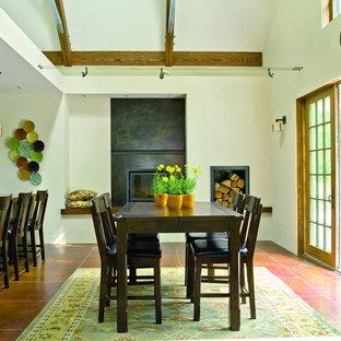Foto di una sala da pranzo aperta verso la cucina chic di medie dimensioni con pavimento in cemento, pareti bianche, camino classico, cornice del camino in cemento e pavimento marrone