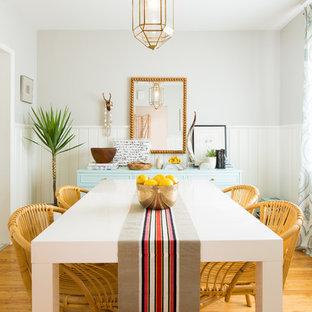 Idées déco pour une salle à manger bord de mer fermée avec un mur gris, un sol en bois brun et un sol orange.