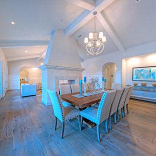 На фото: большая гостиная-столовая в средиземноморском стиле с серыми стенами, паркетным полом среднего тона и двусторонним камином