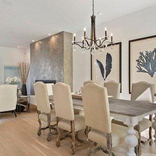 Foto di una sala da pranzo aperta verso il soggiorno tradizionale di medie dimensioni con pareti bianche, parquet chiaro, camino classico e pavimento marrone