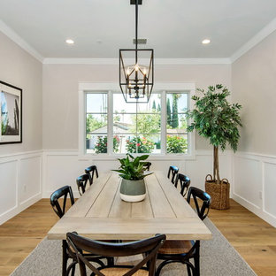 Inspiration for a large farmhouse light wood floor and brown floor enclosed dining room remodel in Phoenix with gray walls