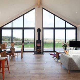 Idee per un'ampia sala da pranzo aperta verso il soggiorno minimal con pareti beige, pavimento in legno massello medio, stufa a legna e cornice del camino in pietra