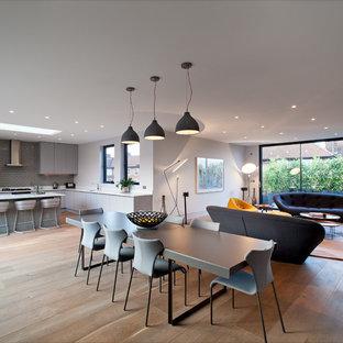Ejemplo de comedor contemporáneo, de tamaño medio, abierto, con paredes blancas y suelo de madera clara