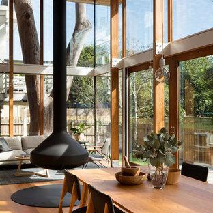 Cette image montre une salle à manger ouverte sur le salon design avec un sol en bois brun et un sol orange.