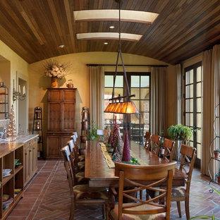 Ispirazione per una sala da pranzo classica con pavimento in mattoni e pareti gialle