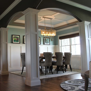 Inspiration pour une salle à manger ouverte sur le salon craftsman avec un mur vert, un sol en bois foncé et un sol vert.