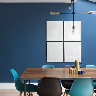 This is an example of a medium sized contemporary dining room in London with blue walls and light hardwood flooring.
