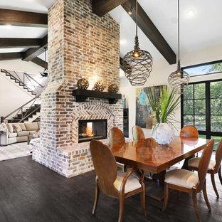 オースティンのトランジショナルスタイルのおしゃれなLDK (ベージュの壁、濃色無垢フローリング、両方向型暖炉、レンガの暖炉まわり、黒い床) の写真