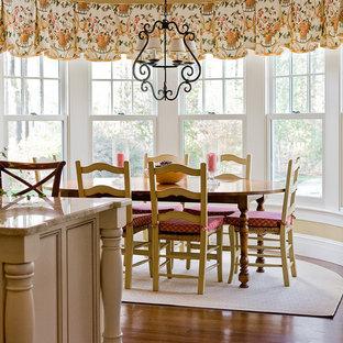 На фото: со средним бюджетом кухни-столовые среднего размера в викторианском стиле с бежевыми стенами, паркетным полом среднего тона, стандартным камином и фасадом камина из камня
