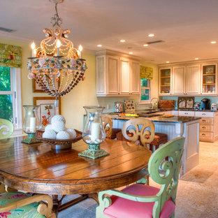 Imagen de comedor de cocina tropical, de tamaño medio, sin chimenea, con paredes amarillas, suelo de travertino y suelo beige
