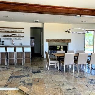 Idee per una grande sala da pranzo aperta verso il soggiorno contemporanea con pareti bianche, pavimento in ardesia, nessun camino, cornice del camino in intonaco e pavimento multicolore