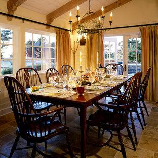 Idée de décoration pour une salle à manger ouverte sur le salon tradition avec un mur jaune et un sol en calcaire.