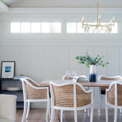 Beach style medium tone wood floor and brown floor dining room photo in Other with white walls