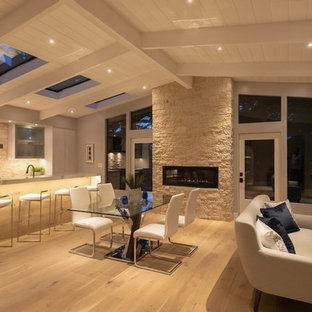 Immagine di una sala da pranzo aperta verso la cucina minimalista di medie dimensioni con pavimento marrone, pareti grigie, parquet chiaro, camino lineare Ribbon e cornice del camino in pietra