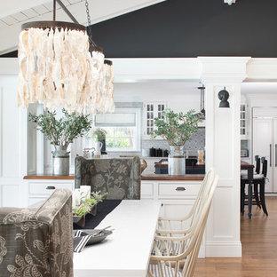 Foto di un'ampia sala da pranzo aperta verso il soggiorno costiera con pareti nere, pavimento in legno massello medio e pavimento rosso