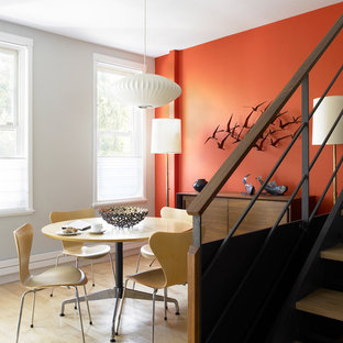 Inspiration for a midcentury modern light wood floor dining room remodel in New York with orange walls