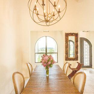 Ejemplo de comedor mediterráneo, grande, abierto, con paredes blancas, suelo de baldosas de porcelana, chimenea de doble cara, marco de chimenea de piedra y suelo gris
