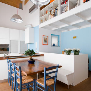 This is an example of an eclectic kitchen/dining combo in Milan with blue walls and medium hardwood floors.
