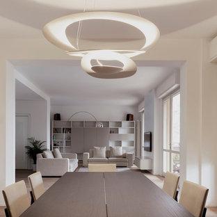 Exemple d'une salle à manger ouverte sur le salon moderne avec un mur blanc et un sol en bois clair.
