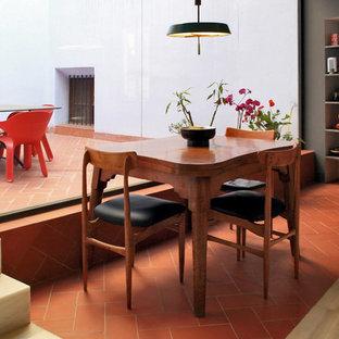 Diseño de comedor de cocina actual, de tamaño medio, sin chimenea, con paredes grises y suelo de baldosas de terracota